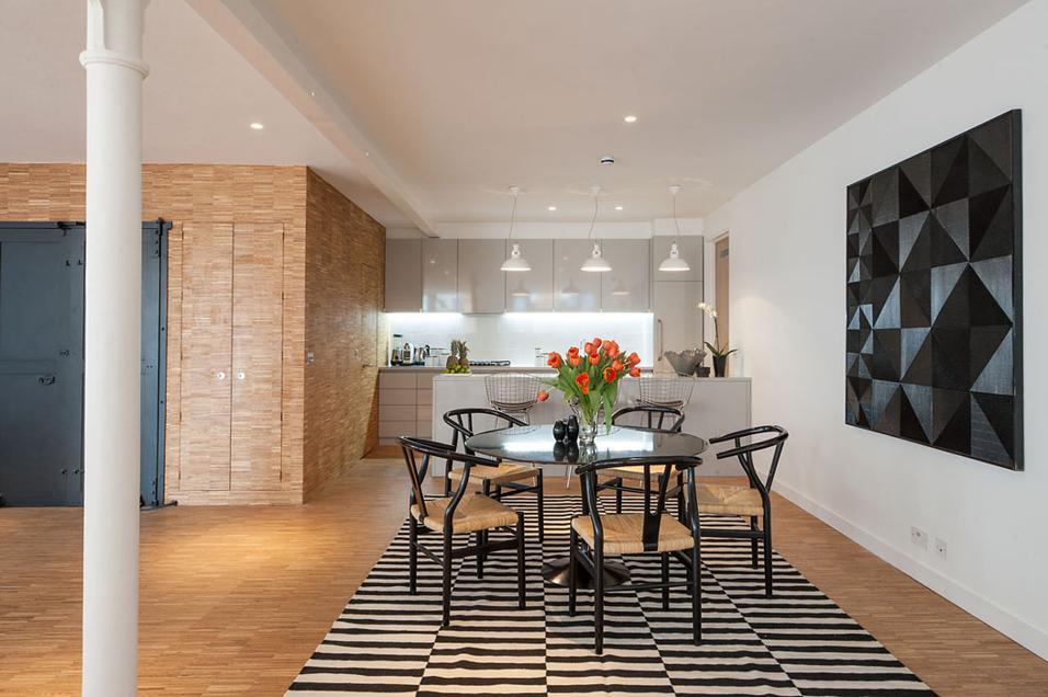 La cucina è separata dall'ingresso dai locali di servizio – ripostiglio e impianti – un volume rivestito in legno che crea una superficie continua con il pavimento in parquet