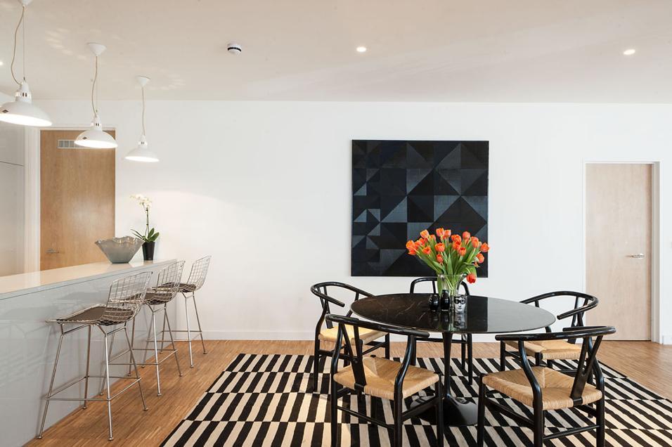 Nella zona pranzo adiacente alla cucina domina il grande tavolo Tulip Dining Table di Knoll, design Eero Saarinen, attorno al quale sono disposte le sedute Wishbone chair di Hans Wegner per Carl Hansen&Son