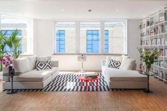 La zona lounge è separata da una libreria a giorno disegnata dagli architetti SIRS. I divani Living White Corner Sofa di Loft Living per Selfridges sono affiancati da un tavolino Tulip Side Table di Knoll International, design Eero Saarinen, e dal tavolino rosso Fluoro Table di Tom Dixon. Il tappeto è Stockholm Rug di Anna Sörensson per Ikea