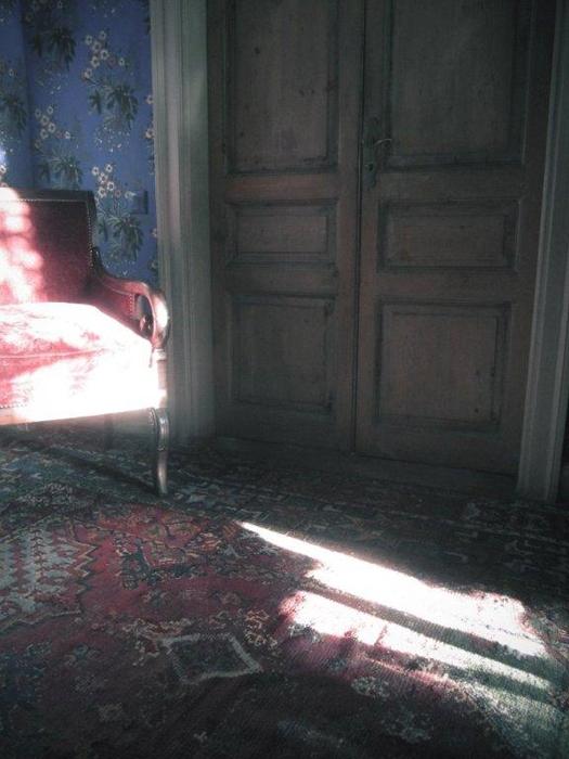La fotografia di Roberto Peregalli coglie bagliori di luce sul tappeto e sul muro con il gusto crepuscolare caro a Proust e che ritroviamo nei progetti di interior dello stesso Peragalli capace di ricomporre suggestioni del passato con oggetti, mobili, stucchi e carte da parati