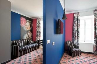 Se passate da Arles per il festival della fotografia, segnatevi questo indirizzo: Jules Cesar, hotel appena ristrutturato dallo stilista Christian Lacroix con l'architetto Olivier Sabran. Lavoro certosino. Letteralmente. Nel XVII secolo il luogo ospitava un convento carmelitano, poi convertito in albergo nel 1928: 'il prediletto' dal gotha della mondanità, da Ernest Hemingway alla duchessa di York. «La storia è stata qui, come non tenerne conto», dice Lacroix, che reinventa i decori partendo proprio dalla tradizione: un po' di stile conventuale (la camera bianca e ocra della Madre Superiora), un tocco di tauromachia (nel ristorante e bar), molti colori locali (rosso, rosa, giallo) e tanta Provenza, estremizzata in grafiche macro e tappeti trompe l'œil. Nella foto una stampa de L'Arlesienne di Antoine Raspal.