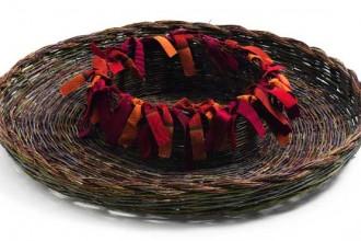 Un cesto intrecciato con arbusti di olivastro e nastri colorati. Designer: Annalisa Cocco