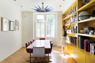 Il giallo della libreria illumina la sala da pranzo. Il lampadario è un modello del 1954 in vetro di Murano mentre le poltroncine portano la firma dell'architetto Martin