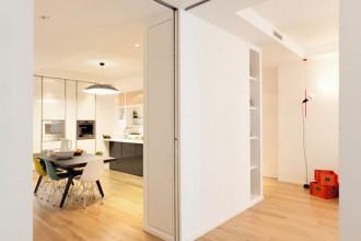 Il sistema di pannelli scorrevoli che dividono gli spazi della zona giorno nell'appartamento a Milano ristrutturato da Wisp Architects. Sulla destra