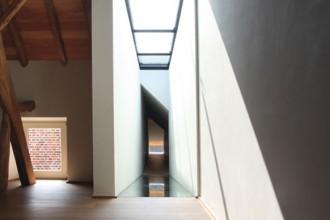 Le travi in legno convivono con gli inserti in vetro che attualizzano l'edificio nella campagna belga