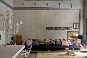 Il divano è formato da un piano in cemento che occupa tutta la parete del living su cui sono appoggiati due larghi materassi neri completamente coperti dai cuscini in tessuto stampato