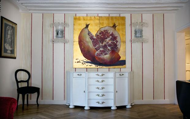 Nel SOGGIORNO le pareti sono dipinte a mano e poi cerate a larghe righe bicolori. Il CASSETTONE di legno bianco e le luci sono opera del designer Adalberto Arcidiacono di Roma. Il grande QUADRO della melagrana spaccata su fondo oro è di Silvio Ottaviani
