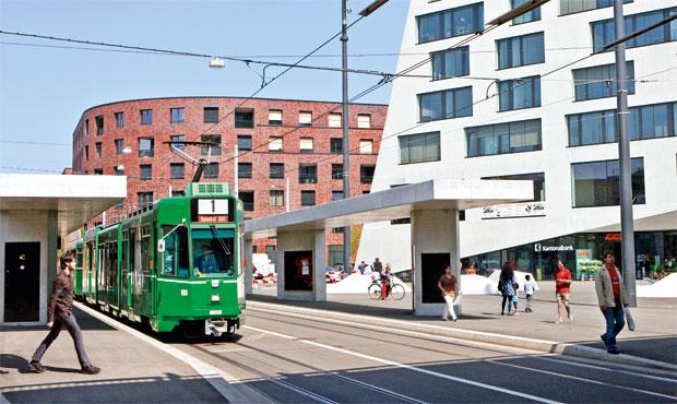 Edifici residenziali in mattoni in contrasto con le forme cubiste in cemento del Volta Center disegnato dagli architetti svizzeri Buchner Bründler. In primo piano il tram della linea 1 che attraversa la città fino ad arrivare alla Stazione Centrale Basel SBB