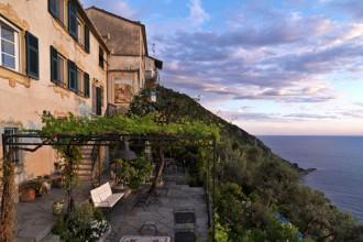La casa a Camogli si sviluppa su tre piani. Sulla terrazza il grosso tavolo per le cene estive è riparato da un pergolato in ferro battuto ricoperto da viti di uva fragola e rincosperno