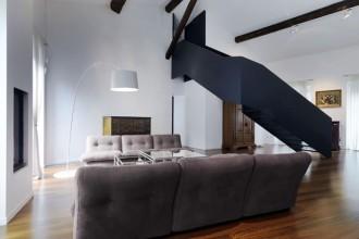 Al primo piano dell'appartamento - a cui è stato unito il sottotetto in modo da formare un unico volume funzionale - uno spazio continuo si sviluppa dalla cucina e accoglie la sala da pranzo. Illumina il tavolo in primo piano la lampada a sospensione Twiggy