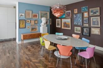 Dietro la parete grigio azzurra della zona pranzo si nasconde la cucina. Il tavolo Tulip di Eero Saarinen per Knoll è circondato dalle sedie di Fritz Hansen laccate in vari colori (design Arne Jacobsen). Al centro