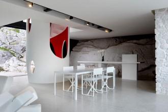 La collina azzera i confini tra interno ed esterno diventando sfondo naturale della sala da pranzo. Il confronto con la roccia è enfatizzato dal minimalismo e dal rigore dell'arredamento scelto