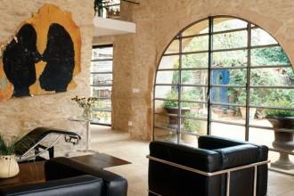 Esterno e interno comunicano visivamente attraverso le grandi aperture ad arco del living: arredato con un grande tavolo di acciaio Corten e chaise longue e poltroncine serie LC di Le Corbusier (prodotte da Cassina).