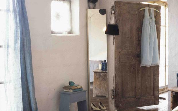 Il letto in ferro battuto verniciato di bianco appoggia sulla muratura grezza intoncata in modo grossolano