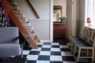 La robusta scala in legno adibita a libreria appoggia sul parquet dipinto a scacchi neri e bianchi