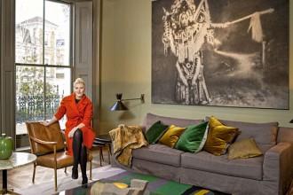Faye Toogood posa sulla poltroncina in legno e pelle Crillon dell'azienda britannica Soane. Accanto