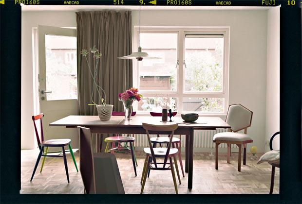 Zona pranzo. Le sedie arcobaleno sono una reinterpretazione di Martino Gamper di un classico del marchio Ercol. Sopra un lampadario scandinavo di modernariato. Vasi e ciotole sul tavolo sono opera di Francis. Lo zenzero d'argento è del designer tedesco Karl Fritsch