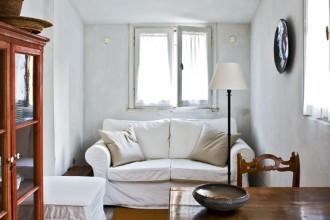 Il divano bianco e la credenza a vetri arredano l'ingresso-soggiorno- pranzo in uno stile tra classico e rustico; di provenienza Umbra le sedie. Collegata al soggiorno la cucina.