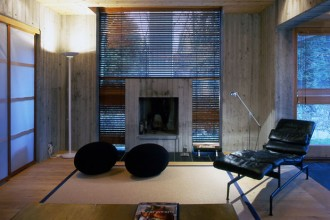 Legno chiaro e cemento rivestono gli interni e la facciata esterna dell'abitazione. Il camino è incassato nella grande vetrata del salone