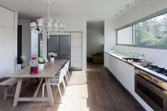 I mattoni a vista dipinti di bianco del muro esterno si ritrovano in cucina
