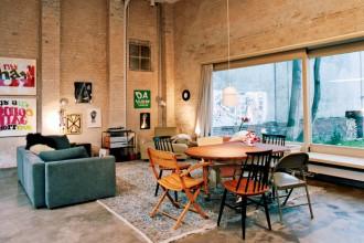 Casa galleria. Nel living tavolo da pranzo e divano sul grande tappeto persiano di famiglia