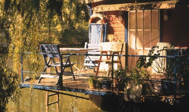 Sembra un angolo di paradiso naturale e invece è Berlino. Acqua e vegetazione fanno da sfondo alla veranda a sbalzo situata sul retro della casa galleggiante di Michael Haberkon. Ad arredarla: tipiche sdraio da giardino
