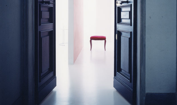 Vista dell'ingresso dal vano scale. Sul pavimento bianco spicca uno sgabello vintage con fodera rossa. Sulla mensola in alto: scatole di latta anni '60