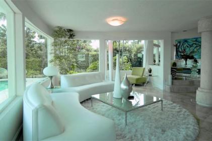 Colonne e pavimenti in marmo nel salone di questa villa a Miami. Le grandi vetrate trasparenti si affacciano direttamente sulla piscina. Il tappeto è di Eclectic Elements