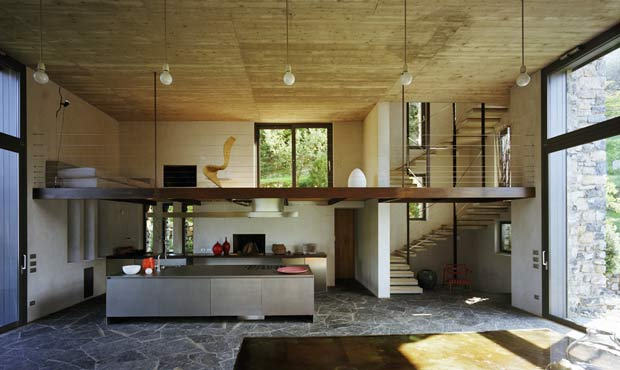 Il doppio livello della zona giorno con soppalco. La modernità del cemento a vista sposa la tradizione dei materiali locali