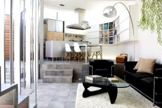 L'ambiente principale della casa che unisce salotto e cucina: come per tutti gli interni della casa la luce naturale entra dalla parete a vetri che guarda al cortile interno