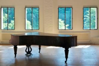 A sinistra: pianoforte a coda austriaco fine '800 in stile Biedermeier sul pavimento in tavole di abete. A destra: camino realizzato su disegno in lamiera di ferro naturale. Poltroncina 'Deck chair' Lido (1938) disegnata a metà anni '30 per il lido di Locarno