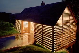 Di notte la luce interna filtra attraverso le pareti in vetro laminato e legno di quercia
