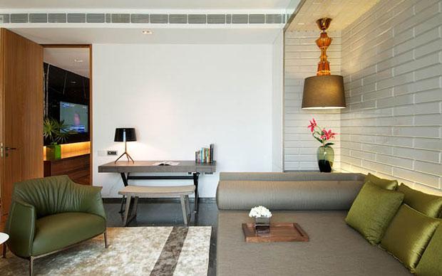 Il living della casa giocato tra le tonalità del legno e le tonalità neutre del divando Bend Sofa di B&B Italia