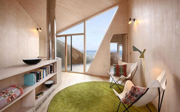Il living della Dune House con il camino ritagliato nella parete in cemento. Da notare il soffitto in legno che si allaccia al piano superiore