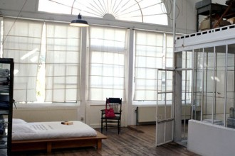 Le grandi vetrate sono uno dei punti di forza dell'atelier-abitazione di Eugènie. Schermate con teli bianchi realizzati su misura