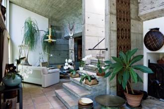 L'ampio soggiorno  di casa Gochkausen.  Il cemento a vista disegna pareti e soffitto. A terra: grandi piastrelle di cotto grezzo. Poltrona