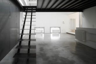 Il lungo fronte di cemento a vista dell'ex fabbrica. Trasformata da Mdu in loft a schiera