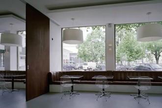 Divanetti in pelle ad incasso e sedie superleggere in metallo: l'area luonge che funziona come sala per la prima colazione