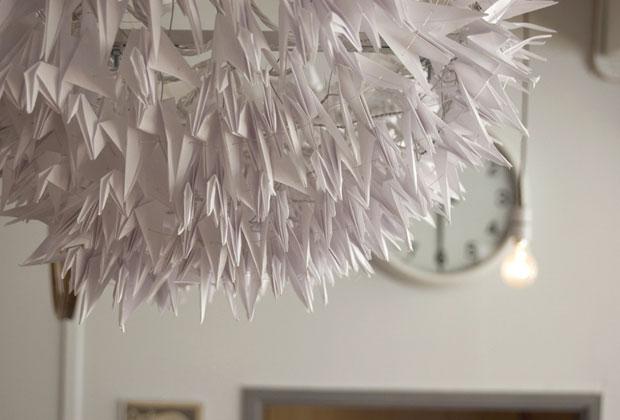 Birds' Cloud è la scultura luminosa firmata da Elena Comincioli. Un lampadario di 300 origami e 60 led