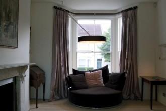 Gli interni della casa in Souldern Road a Londra. I tre fari montati sulla colonna illuminano il soggiorno con discrezione