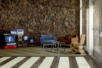 Un mixer targato Facebook troneggia davanti ai divani della zona conversazione. L'Alcove Highback Sofa di Ronan & Erwan Bouroullec per Vitra fa da paravento. La rampa collega la lounge con il campo di basket