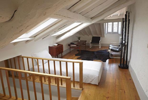 Travi bianche e pavimento in legno chiaro per la camera mansardata arredata come una piccola casa