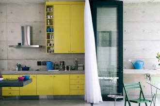 La cucina della casa di Johannesbourg: piano in cemento e mobili gialli