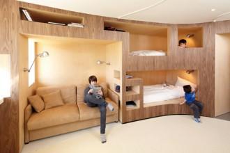 Una zona dell'area living della casa dove è subito chiara la continuità delle funzioni domestiche che si alternano all'interno del grande volume in legno