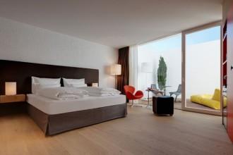 La stanza fragola - Erdbeere in cui spicca il dettaglio cromatico della sedia Swan di Arne Jacobsen.