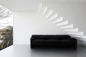 La scala che collega i due piani dell'abitazione. La vetrata occupa tutto lo spazio della parete