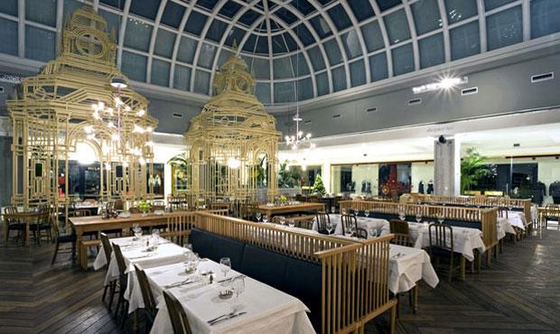 Nel café di Istinye i grandi elementi metallici creano isole per i tavoli più grandi. In primo piano le sedute sono custom-made e servono ad articolare lo spazio interno