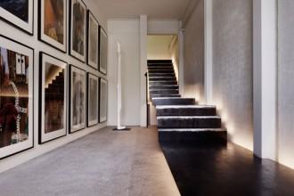 La scala in acciao sospesa che consente l'accesso all'abitazione. Di fianco la scultura Cycladic di Barry Thompson. Le maxi stampe sono scatti fatti durante i viaggi dell'architetto nel Nord dell'Africa e in India