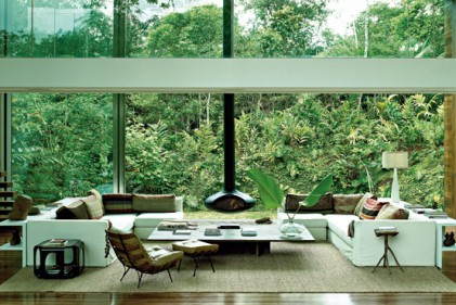 Le grandi vetrate proiettano l'ambiente del living nella foresta con un effetto scenografico. Rigorosi divani bianchi incorniciano il tappeto del designer brasiliano Nani Chinellato. La poltrona con poggiapiedi anni 60 è un pezzo di famiglia