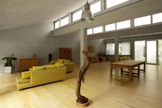 L'area living del loft a Lecco ristrutturato dall'architetto Arturo Montanelli. Divani giallo senape Flexform